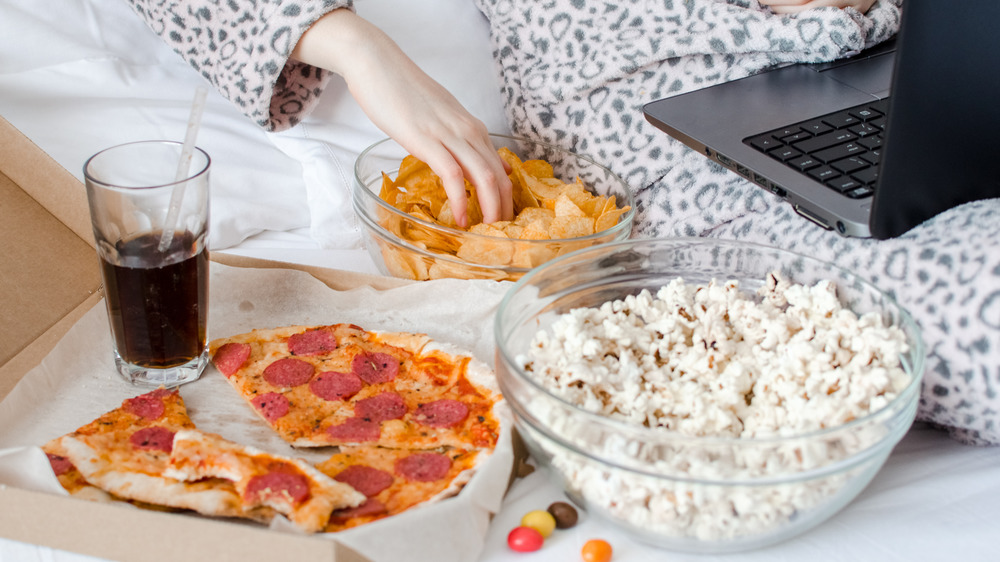 Movie snacks in bed with person in pajamas