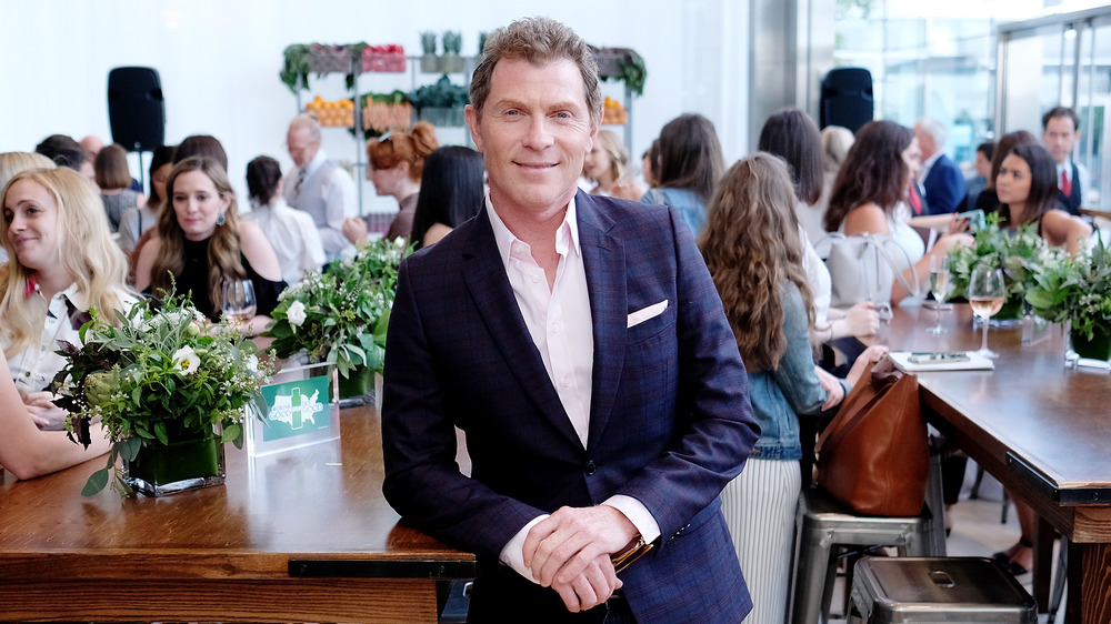 bobby flay leaning on wooden counter