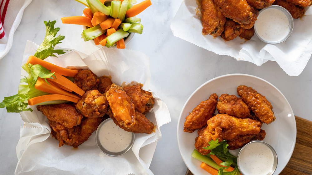 buffalo wings on white surface with celery and carrots