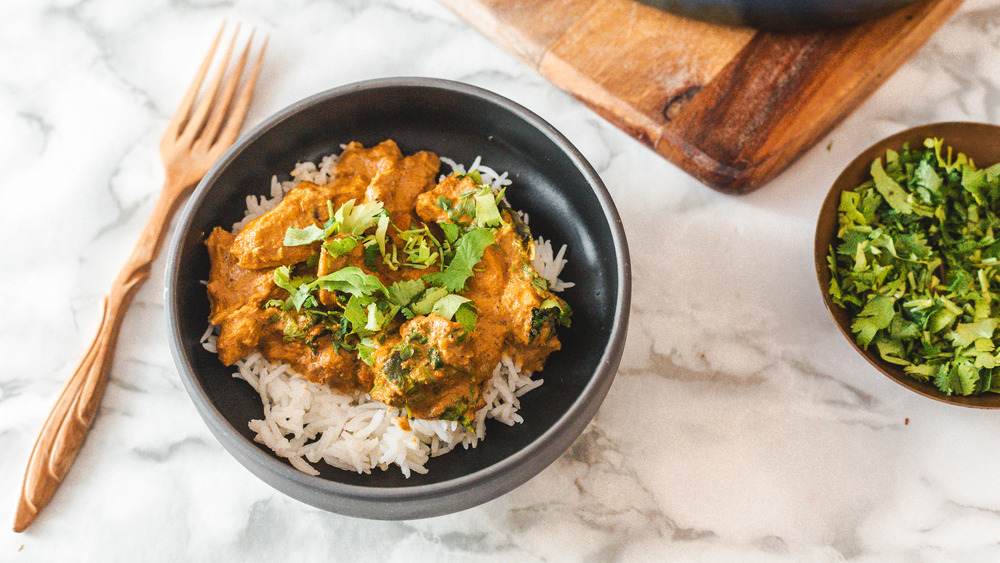 bowl of butter chicken next to cilantro