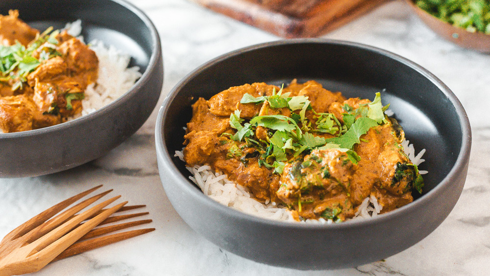butter chicken with rice in bowls