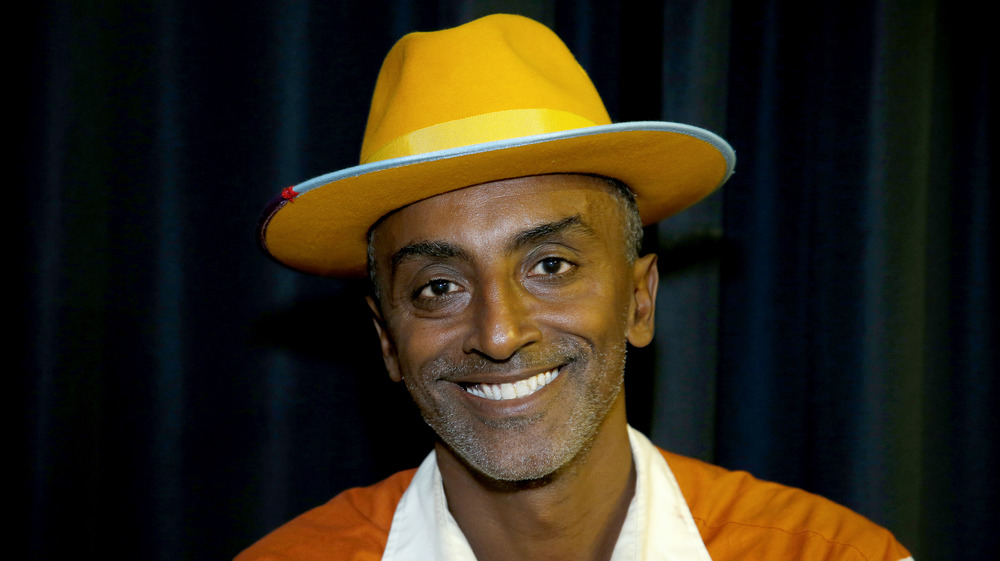 Chef Marcus Samuelsson smiles wearing a hat