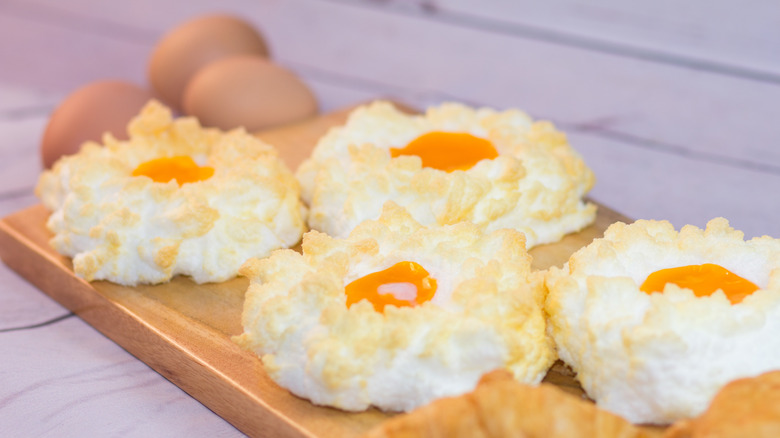 Cloud eggs on a wooden chopping board