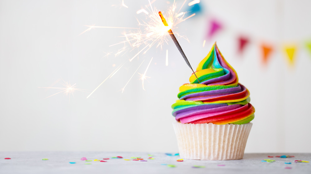 vanilla cupcake with tie-dyed frosting and a sparkler