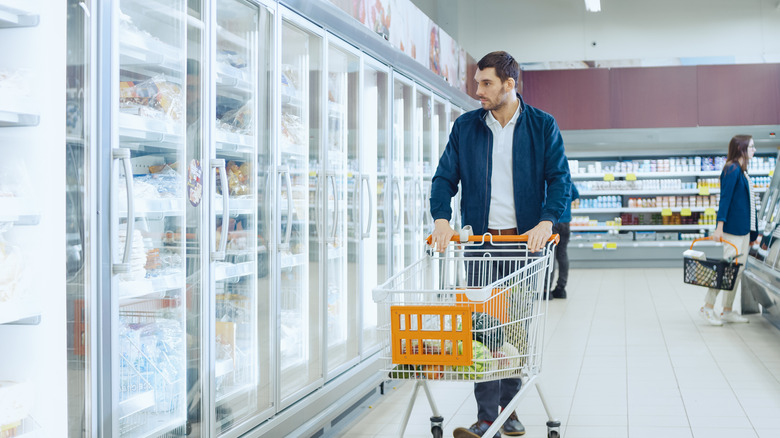 Man pushes cart in freezer section