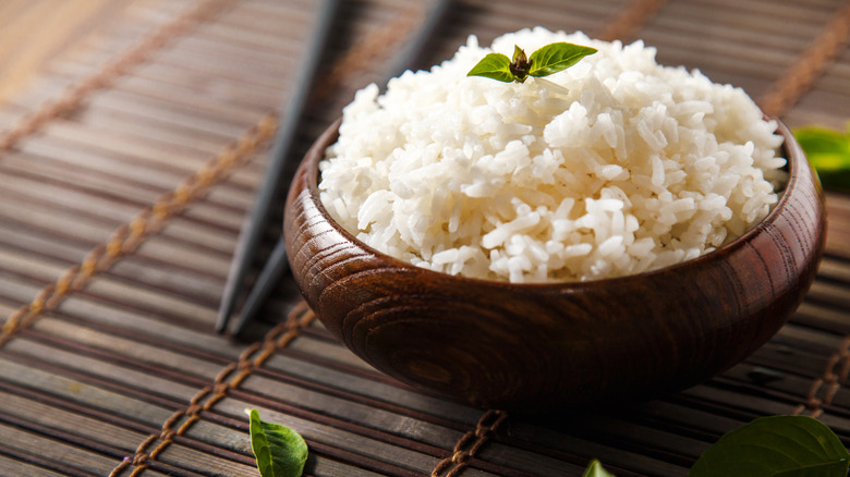 bowl of white rice with chopsticks in background