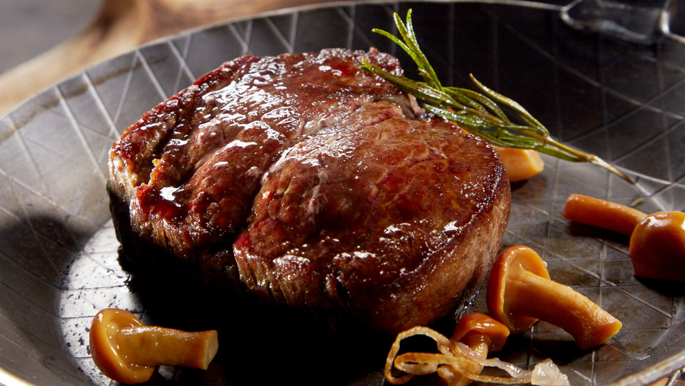 Venison in a pan with rosemary and mushrooms