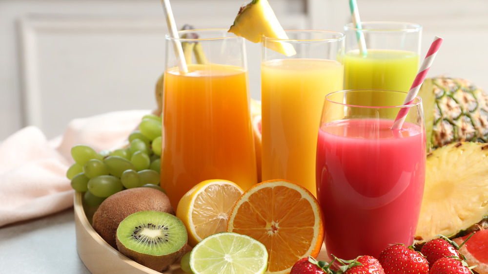 Juice in glasses on fruit-filled tray