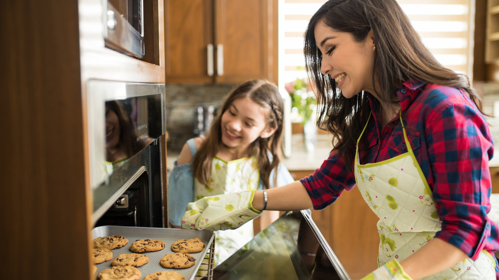 mom and daughter taking cookies from oven