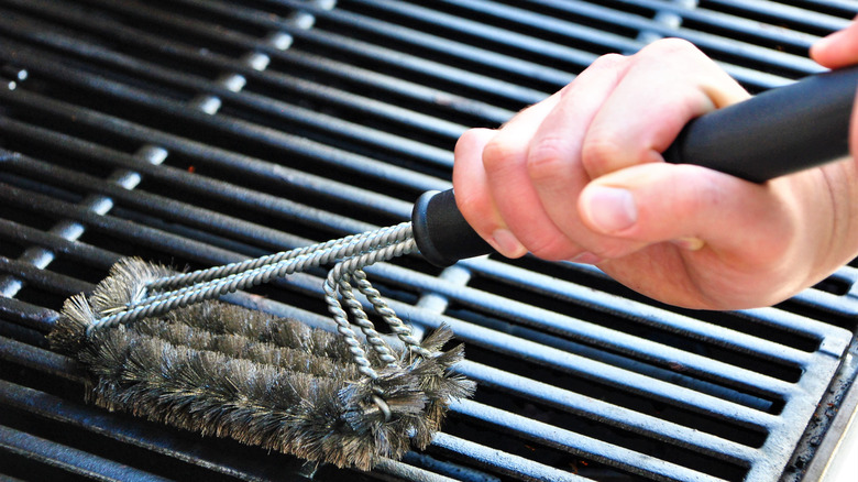 Hands holding grill brush cleaning grill