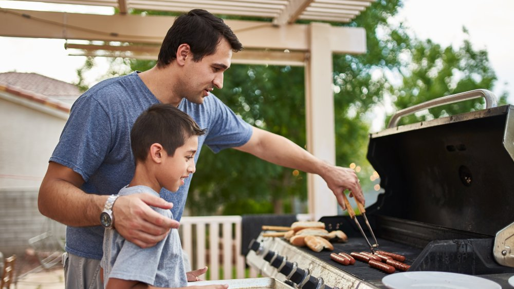dad and son cooking on gas grill