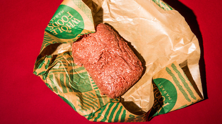 Ground beef in a brown paper wrapper on a red background