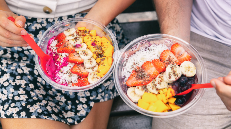 two smoothie bowls with fruit, coconut, and chia seeds
