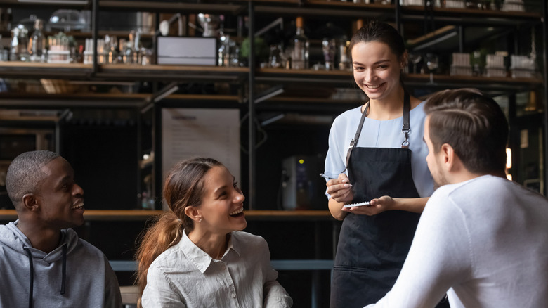 Server taking order from table full of diners