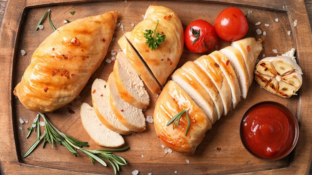Cooked chicken breast with rosemary and tomato on cutting board