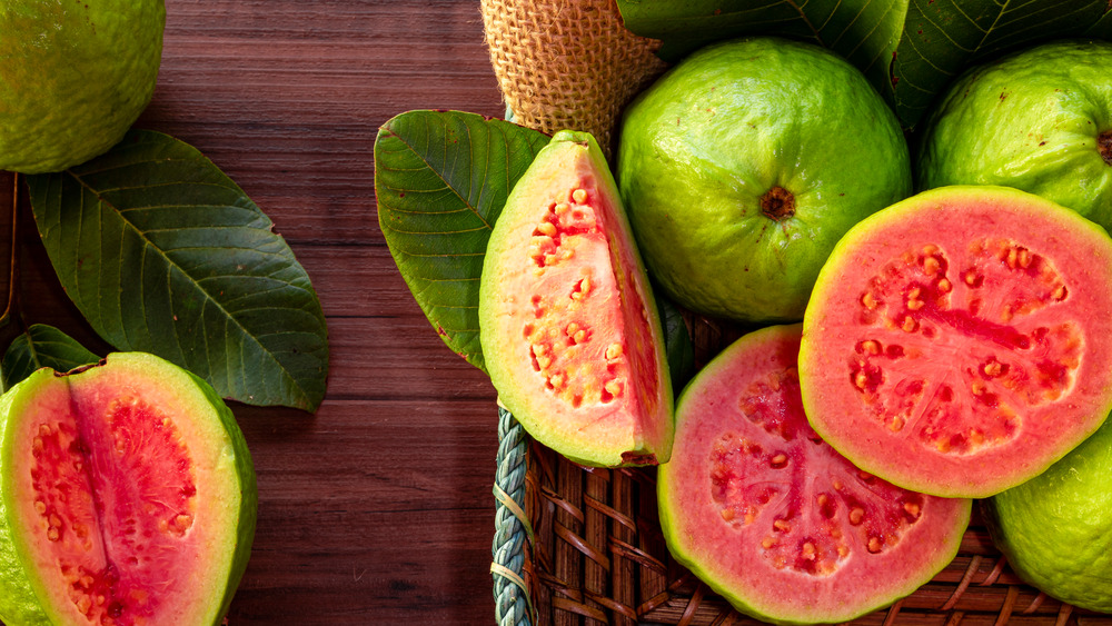 Several sliced guavas on wooden table