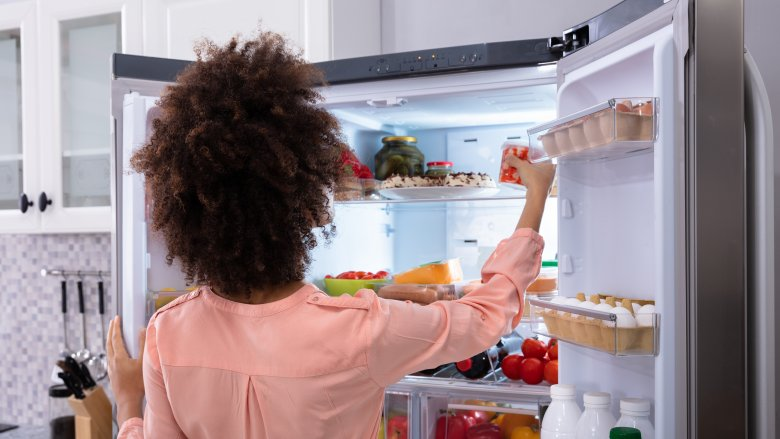 Woman putting food in the refrigerator