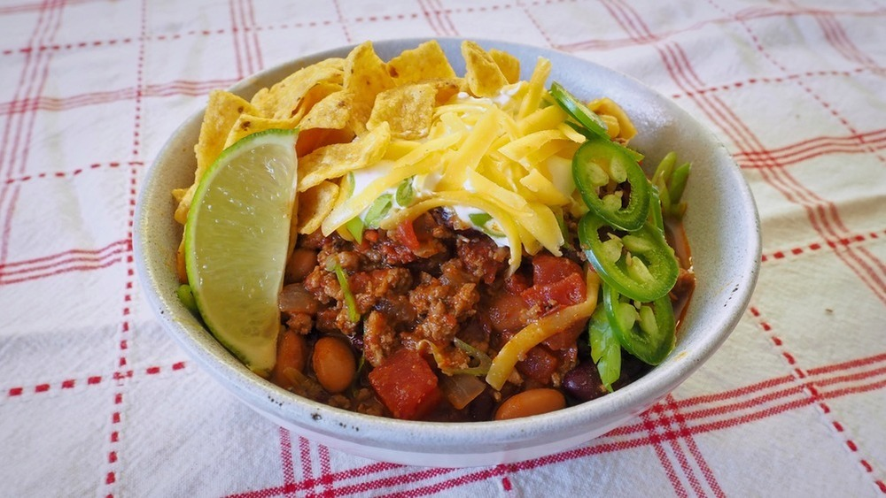 5-ingredient chili in white bowl with lime wedge and jalapeno slices