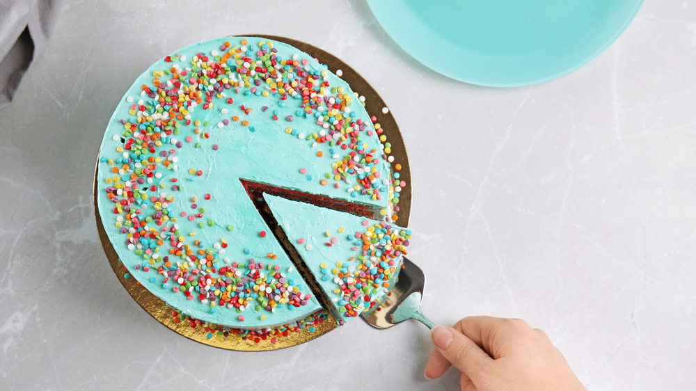 Taking a slice of a piece of cake with blue frosting