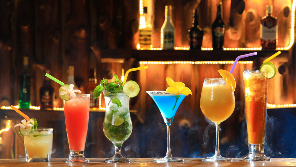 Mixed drinks lined up on a bar