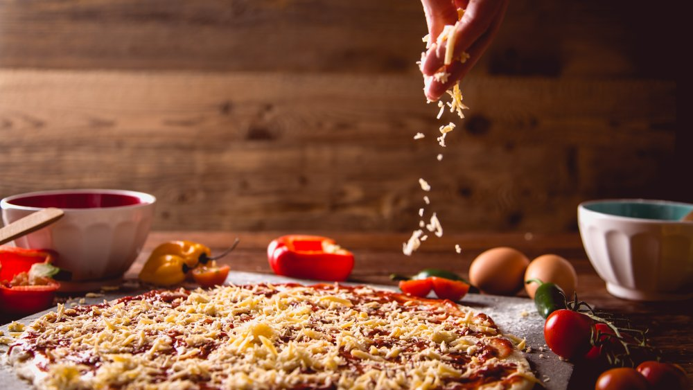 parmesan cheese being sprinkled over pizza