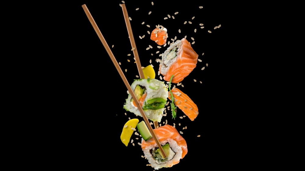 sushi in the air with chopsticks and sesame seeds
