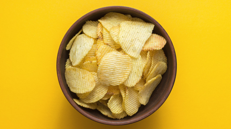 Bowl of potato chips on yellow background