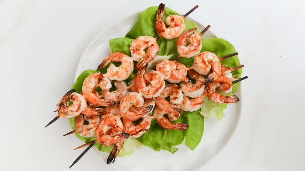 grilled shrimp on skewers with lettuce and white plate