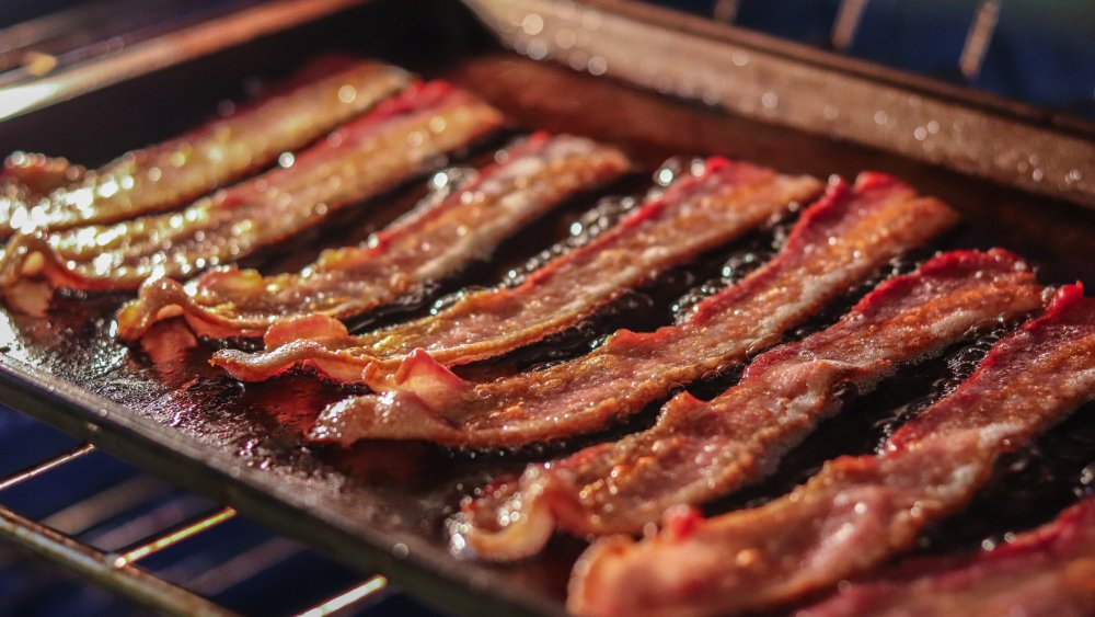Close up of bacon cooking in an oven on a baking sheet.