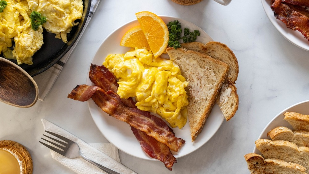 scrambled eggs recipe plated with toast and bacon