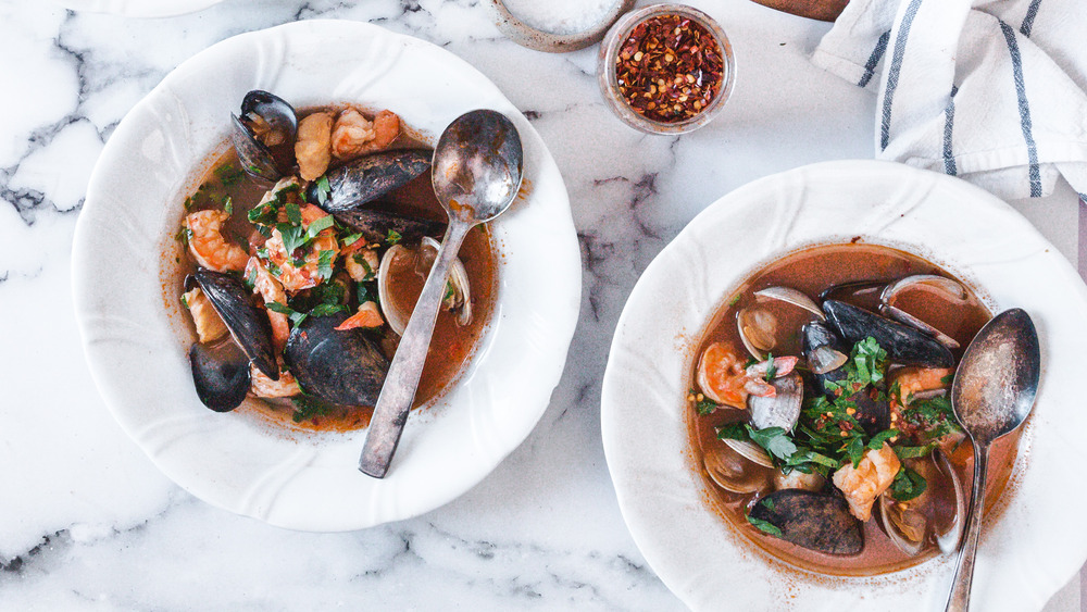 Cioppino seafood stew soup in white bowls with metal spoons