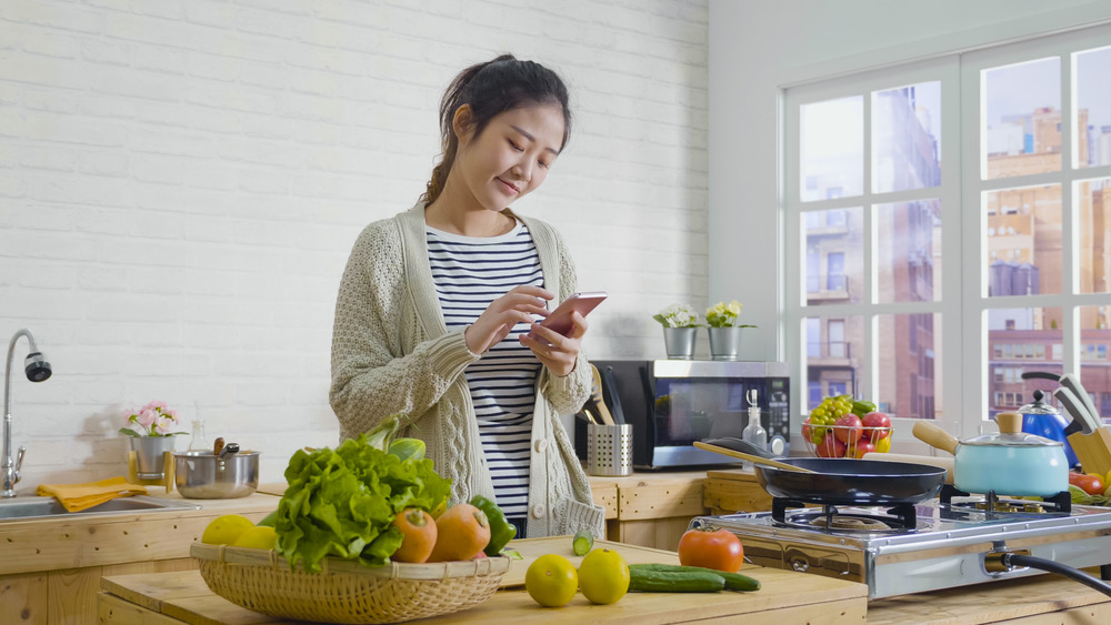 woman cooking with vegetables smartphone