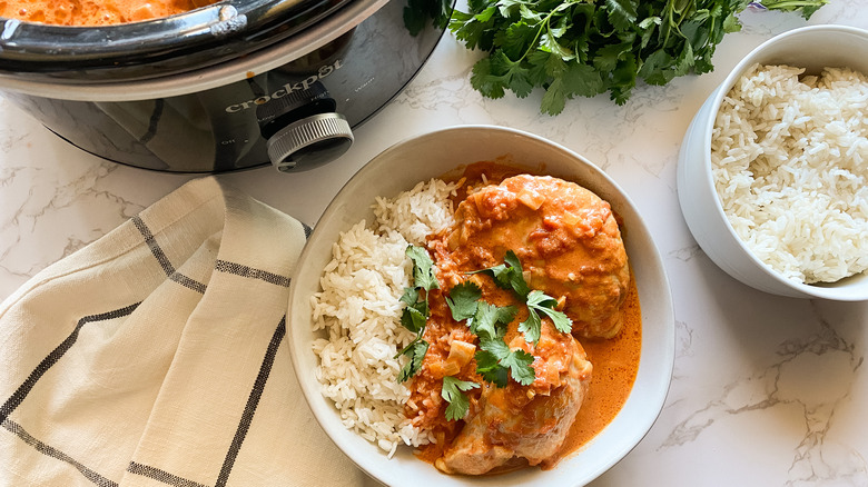 Slow Cooker Butter Chicken served in a bowl with rice and garnish