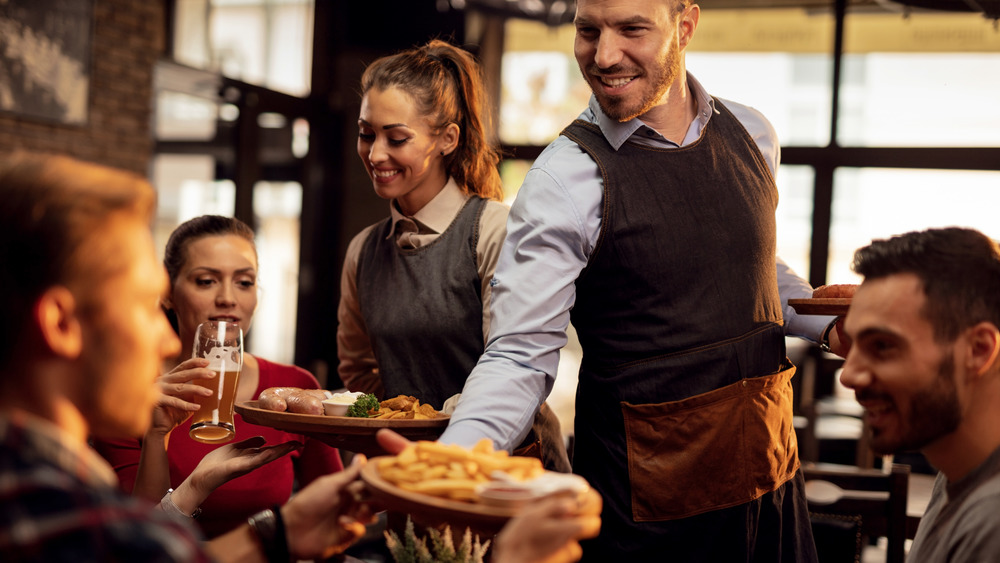 waiter bringing french fries to table