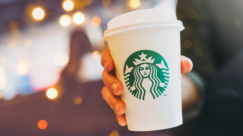 Starbucks coffee cup in person's hand