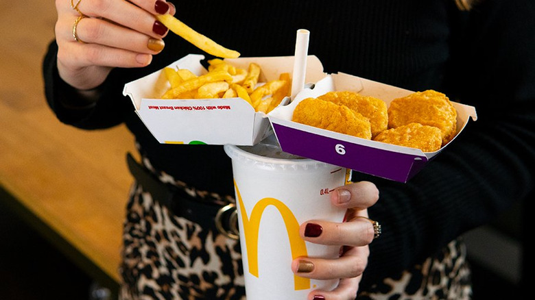 A woman's hands holding McDonald's food
