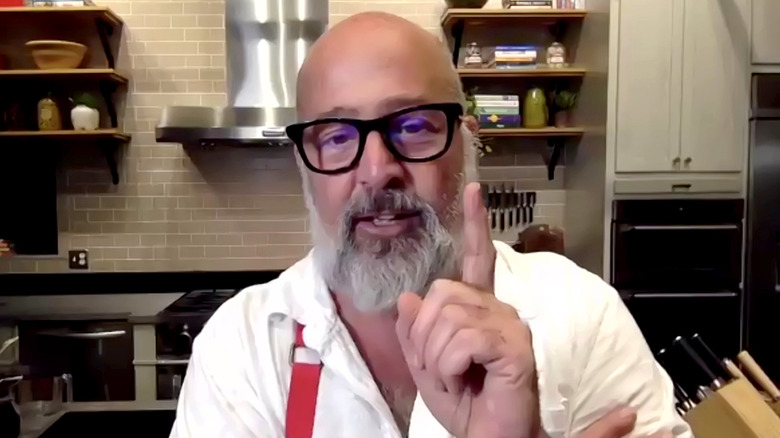 bearded Andrew Zimmern pointing