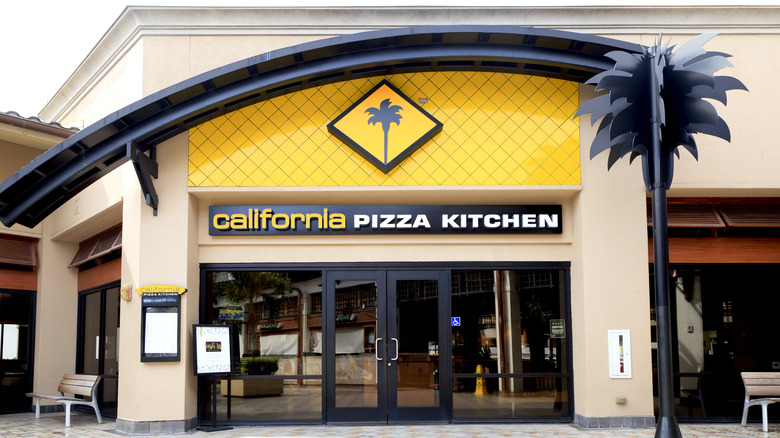 California Pizza Kitchen building next to black palm tree