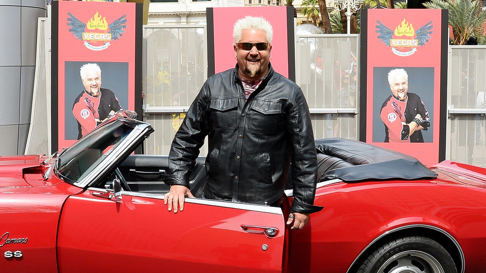 Diners, Drive-Ins and Dives host Guy Fieri smiles in front of red Camaro