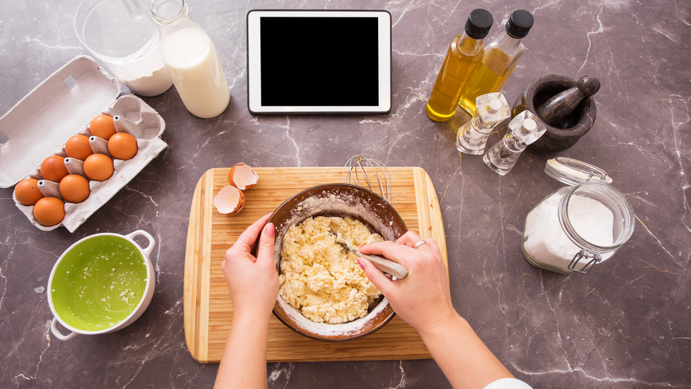 Woman making dough with tablet