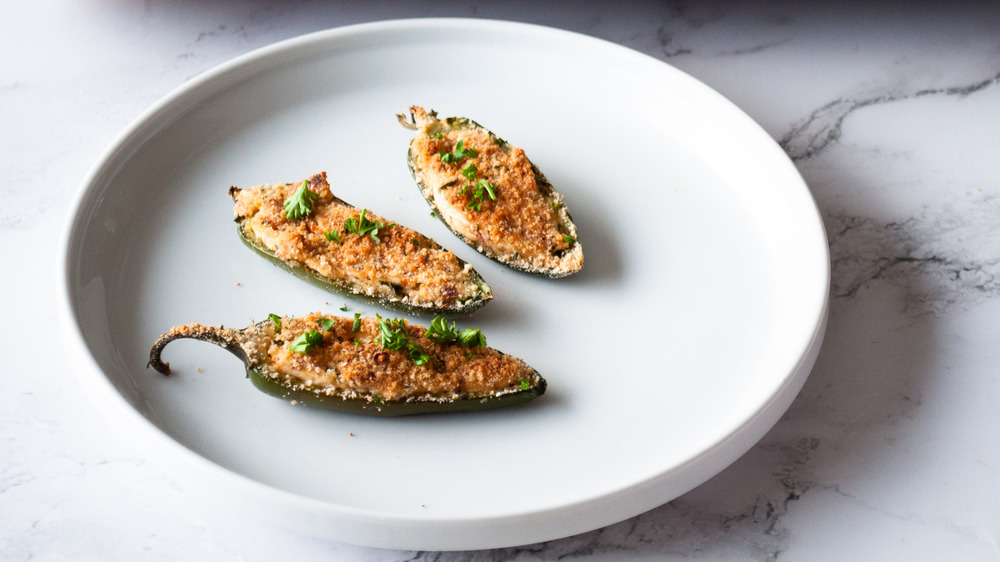jalapeno poppers with bread crumbs and bacon on white plate