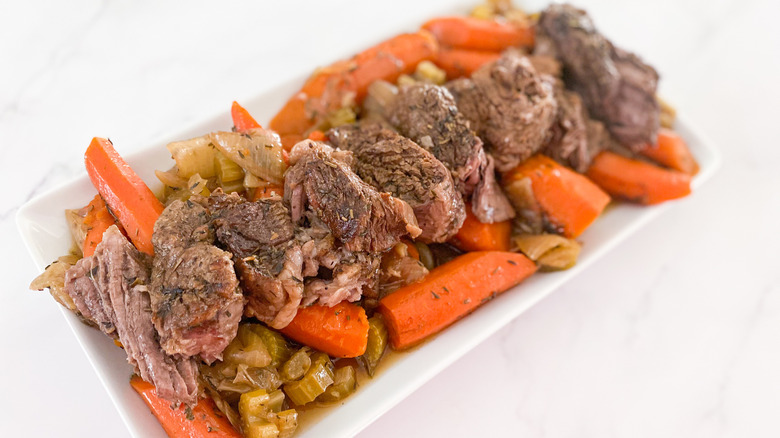 roast beef on platter with carrots and celery