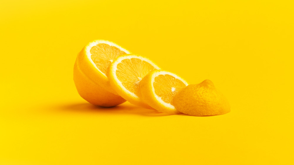 Sliced and halved lemon on yellow background