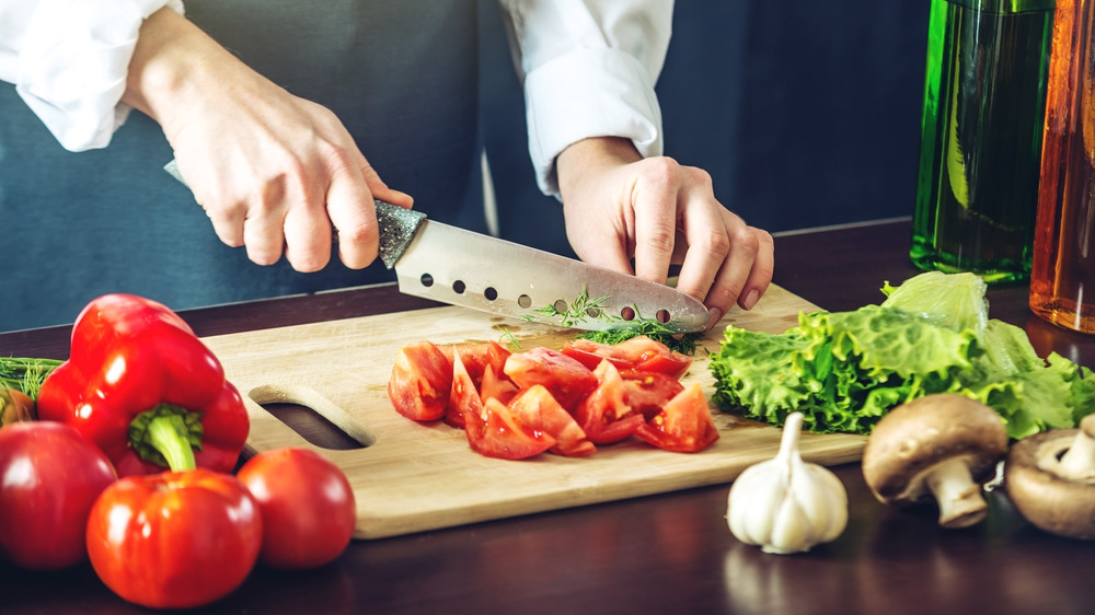 Person chops tomatoes on a cutting board
