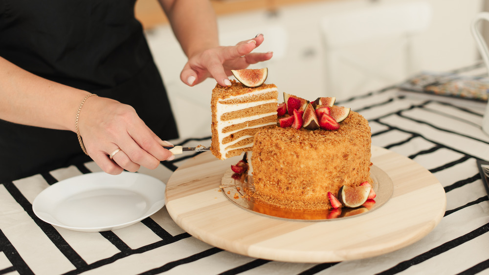 Baker cutting into a layered honey cake