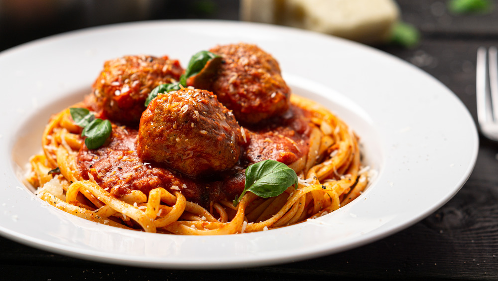 A bowl of spaghetti and meatballs with basil