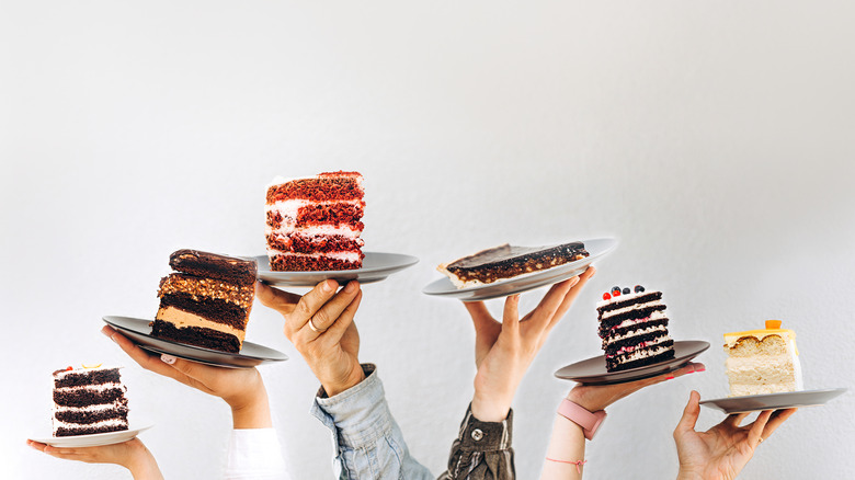 Hands holding different slices of cake on plates