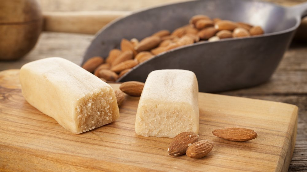 Bars of marzipan with almonds on cutting board