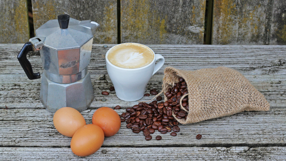 Coffee maker, coffee beans, and brown eggs setting on a wood table