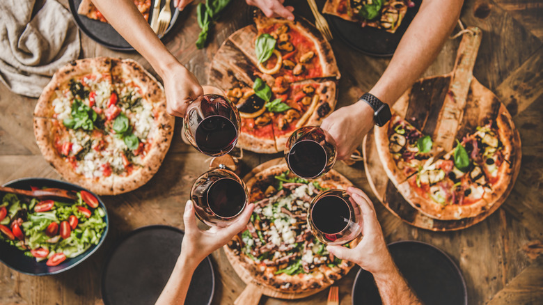 People reaching over table full of pizzas